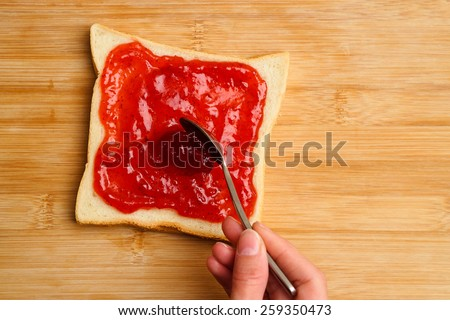 Woman making sweet sandwiches with berry jam - stock photo