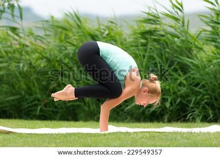 Woman making yoga crow pose - stock photo