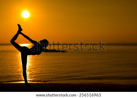 Woman making yoga on the beach in sunset - stock photo