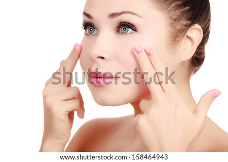 Woman massaging her face with her fingers, white background - stock photo