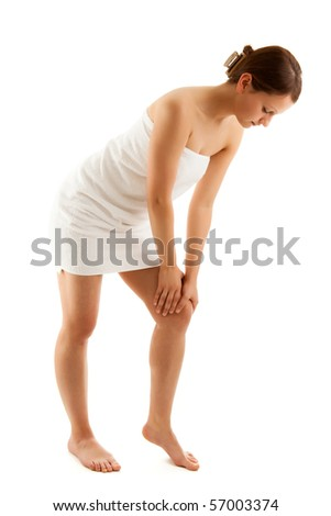 Woman massaging pain knee isolated on a white background - stock photo