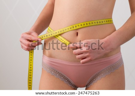 woman measures the waist with a yellow measuring tape - stock photo