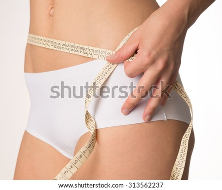 Woman measuring her waist circumference / waist circumference - stock photo