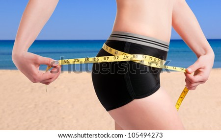 Woman measuring her waist with a yellow measuring tape. Beach background. - stock photo