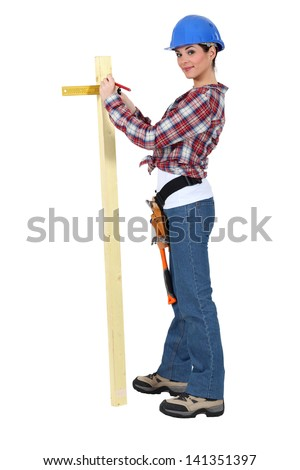 Woman measuring the width of a plank of wood - stock photo