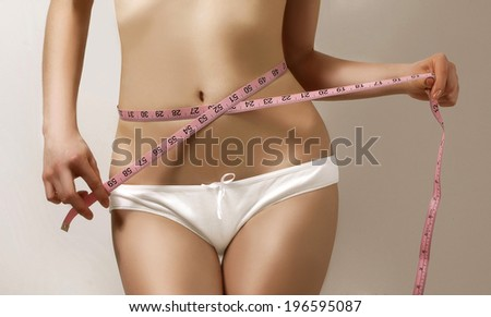 Woman measuring waistline, fitness and diet  - stock photo