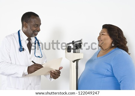 Woman measuring weight while doctor writing notes in clinic - stock photo