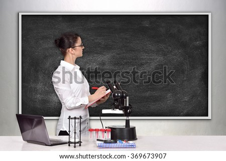 woman medical or scientific researcher in laboratory and looking on blank blackboard - stock photo