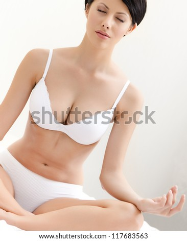 Woman meditates sitting on the bed, - stock photo