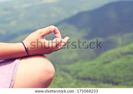 Woman meditating at mountain forest background - stock photo