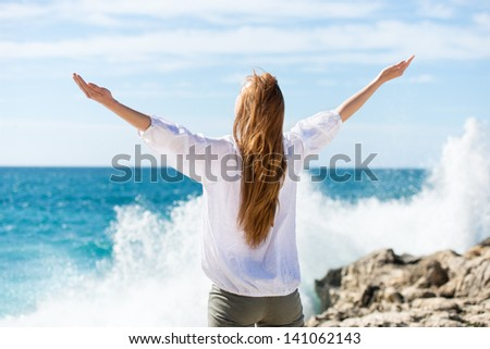 Woman meditating at the sea standing with her arms outspread facing away from the camera towards the ocean on a beautiful sunny day - stock photo