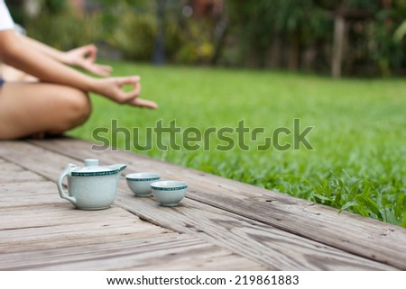 Woman meditating by the water with tea pot - stock photo