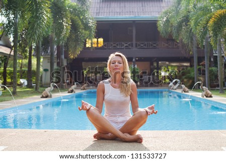 woman meditating near swimming pool - stock photo