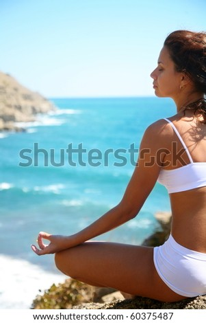 Woman meditating on a rocky seashore - stock photo