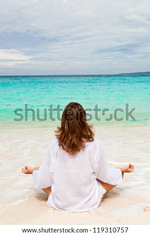Woman meditating on beach in lotus position - stock photo