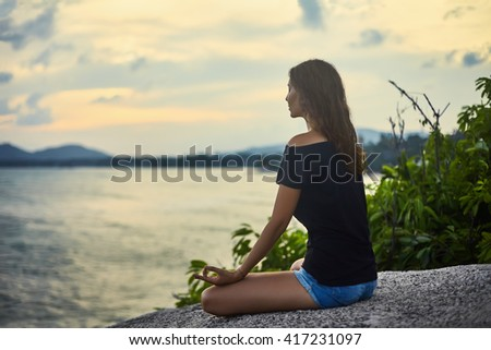 Woman meditating on rocky cliff with sea view - stock photo
