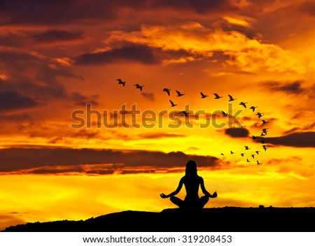 woman meditating on the lake - stock photo