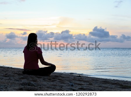 Woman meditation on the beach - stock photo