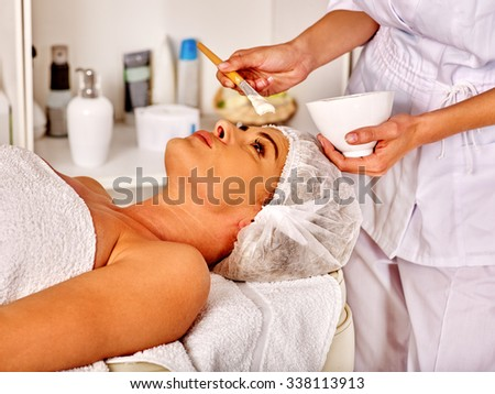 Woman middle-aged in spa salon receiving facial mask by  beautician. - stock photo