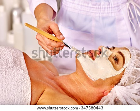 Woman middle-aged look up take facial and neck clay mask in spa salon. - stock photo