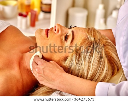 woman middle-aged take face cleaning procedure in spa salon. - stock photo