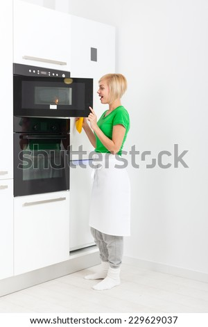 woman modern kitchen appliance setting, young girl housewife cooking oven at home - stock photo