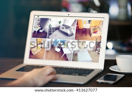 Woman monitoring home security cameras on laptop. Home security system concept - stock photo
