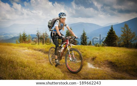 Woman mountain-bike riding on ridge with Carpathian Mountains - stock photo