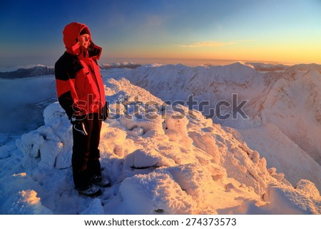 Woman mountaineer admires the sunset from a snow covered mountain summit above the clouds - stock photo