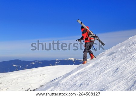 Woman mountaineer carrying the skies on the backpack along steep ridge covered with snow - stock photo