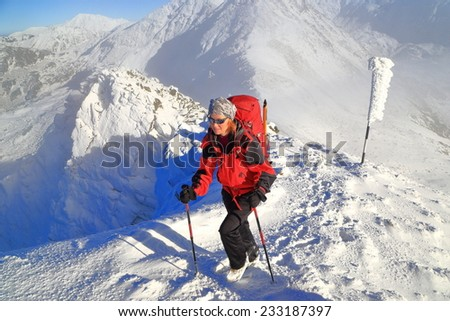 Woman mountaineer walking on snow covered mountain above clouds - stock photo