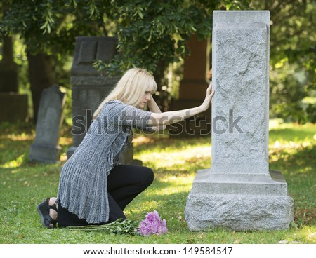 Woman mourns  with her hand on headstone in cemetery - stock photo