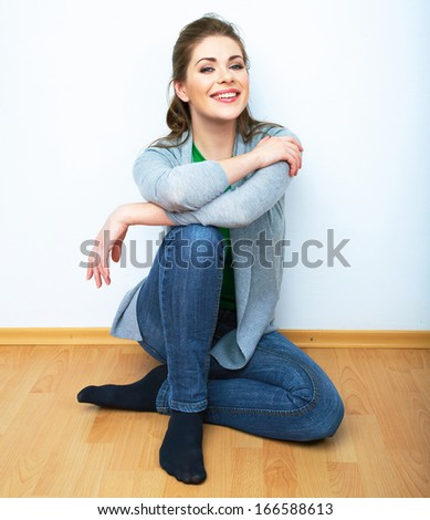 Woman natural portrait. Smiling girl seat on a floor. White background isolated. - stock photo