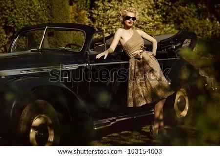 Woman near a retro car outdoors - stock photo