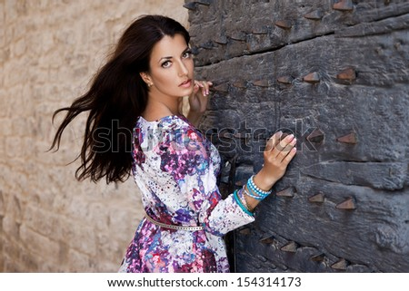 woman near the gate with spikes - stock photo