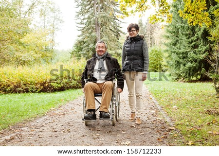 Woman next to man in wheelchair - stock photo