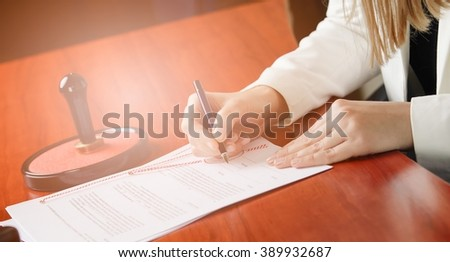 Woman Notary Public signing the contract in her office. Law office - stock photo