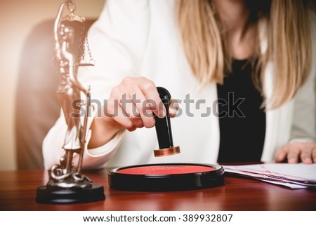 Woman Notary Public stamping the Power of attorney. Law office. - stock photo