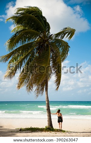 Woman observing Caribbean sea on sandy beach in Varadero on Cuba leaning on palm tree. - stock photo
