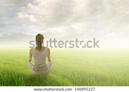 Woman of brunet hair sit on grassland against sunrise or sunset, concept of leisure, lifestyle, healthy, zen etc with good copyspace on heaven. - stock photo