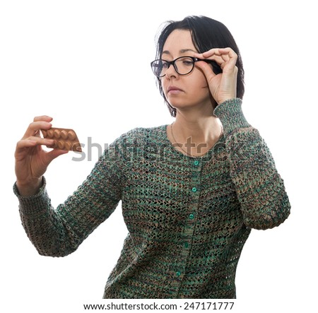 Woman of forty years in reading glasses, looks at medicament - stock photo
