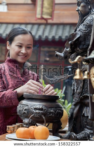Woman offering incense at temple - stock photo