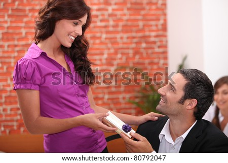 Woman offering man a small gift - stock photo