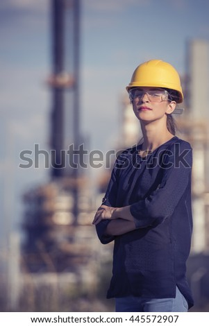 woman oil engineer is standing in front of a refinery - stock photo