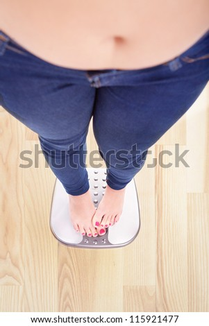 Woman on a bathroom scale hiding the numbers - diet and overweight concept - stock photo