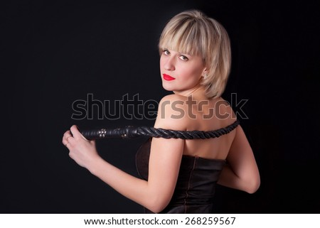 Woman on a black background with a whip in her hand - stock photo