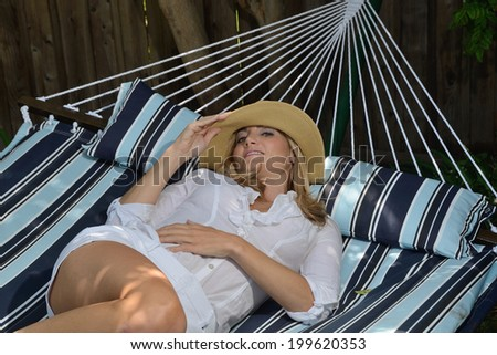 Woman on a enjoying her rest on a hammock/Woman on hammock/Beautiful woman resting on a hammock on a summer day - stock photo