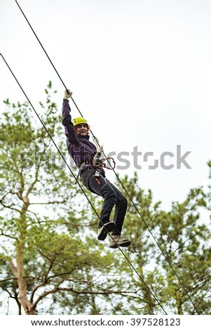 Woman on a high wire climbing in an adventure park - stock photo