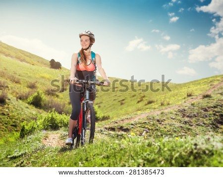 Woman on a mountain bike rides in the mountains of the beautiful nature. Portrait of a girl cyclist outdoors. - stock photo
