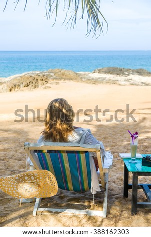 Woman on a sun lounger on a tropical beach with hat - stock photo